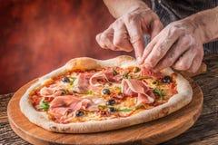 Pizza i szef kuchni Szef kuchni w restauraci przygotowywa deco i pizzę Zdjęcia Stock