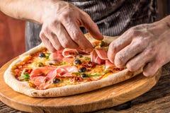 Pizza i szef kuchni Szef kuchni w restauraci przygotowywa deco i pizzę Zdjęcia Royalty Free
