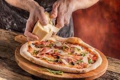 Pizza i szef kuchni Szef kuchni w restauraci przygotowywa deco i pizzę Zdjęcie Stock