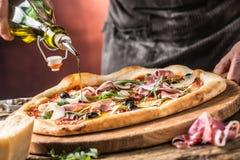 Pizza i szef kuchni Szef kuchni w restauraci przygotowywa pizzę i nalewa Zdjęcie Royalty Free