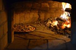 Pizza i ugnen arkivfoto