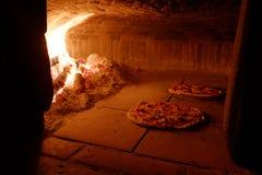 Pizza im hölzernen Ofen Stockfoto