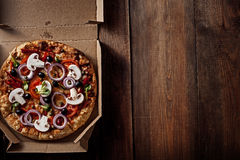 Pizza in im Lieferungskasten auf dem Holz Lizenzfreie Stockfotos