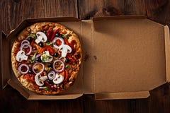 Pizza in im Lieferungskasten auf dem Holz lizenzfreies stockfoto