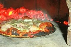 Pizza im Ofen Stockfotos