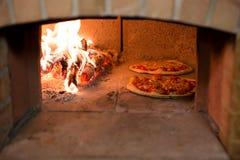 Pizza im Ofen Stockbild