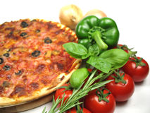 Pizza and ingredients. A delicious homemade pizza and some ingredients stock photo