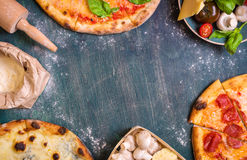 Pizza and ingredients background. Pizza with assorted toppings and ingredients background. Space for text. Pizza, flour, cheese, tomatoes, basil, pepperoni royalty free stock image