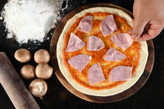 Pizza and ingredients for pizza. On the wooden background royalty free stock photo