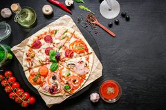 Pizza with ingredients, spices, oil and vegetables on dark table. Flat lay, top view. stock photos