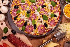 Pizza and ingredients on a table - top view, closeup Stock Photo