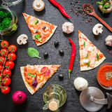 Pizza with ingredients and vegetables on dark table. Flat lay, top view. Sliced pizza pattern royalty free stock images