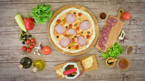 Pizza with ingredients on wooden plate on the table - stop motion animation, 4K stock video footage