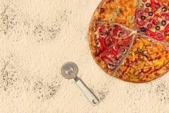 Pizza internacional enorme en fondo de la harina Imagenes de archivo