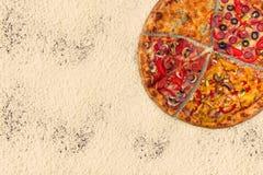 Pizza internacional enorme en fondo de la harina Foto de archivo libre de regalías