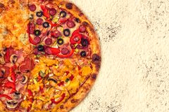 Pizza internationale énorme sur le fond de farine Image stock