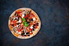 Pizza irritável quente com tomates, mussarela, cogumelos, azeitonas, com referência a fotografia de stock