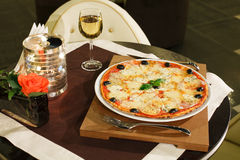 Pizza. Italian pizza with cheese and a glass of white wine Royalty Free Stock Photography