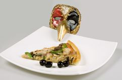 Pizza italian and mask. Still-life about the slice pizza with olives and italian mask.  Studio Stock Photos