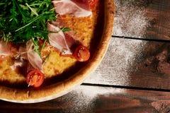 Pizza italiana con el jamón, los tomates y las hierbas en un ½ de madera del ¿del ï de la tabla perder para arriba imagenes de archivo