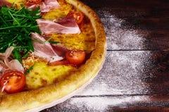 Pizza italiana con el jamón, los tomates y las hierbas en una tabla de madera fotografía de archivo