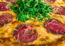 Pizza italiana con el primer de la carne de vaca imagenes de archivo