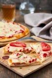 Pizza italiana con el salami, las pimientas y los tomates Imagenes de archivo
