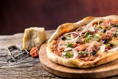 Pizza italiana con il parmigiano dell'olio d'oliva delle olive dei pomodori di prosciutto di Parma Immagine Stock
