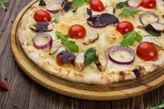 Pizza italiana con il pollo, i pomodori ciliegia, il formaggio e le cipolle o immagine stock