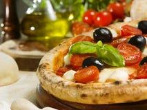Pizza italiana con il pomodoro, la mozzarella e le olive Immagini Stock
