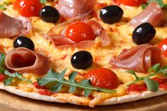 Pizza italiana con il prosciutto e la rucola di prosciutto di Parma macro Immagini Stock Libere da Diritti