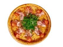 Pizza italiana con il prosciutto, i pomodori e le erbe su un fondo isolato per il menu fotografie stock