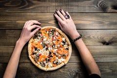 A pizza italiana CORTADA MUITO QUENTE superior da opinião do CLOSE UP com mão toma uma fatia na tabela de madeira com cogumelos,  imagens de stock royalty free