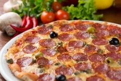 Pizza italiana del salami en la tabla Fotos de archivo libres de regalías