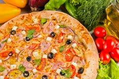 Pizza italiana deliciosa con las aceitunas queso y verduras del jamón Foto de archivo libre de regalías