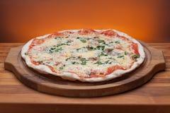 Pizza italiana deliciosa servida en la tabla de madera Imagen de archivo