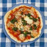 Pizza italiana deliziosa sulla tavola Immagine Stock