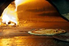 Pizza italiana en un horno ardiente de madera Foto de archivo libre de regalías