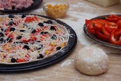 Pizza italiana preparada con la salsa, el queso y otros ingredientes otro en el fondo de madera Imagen de archivo