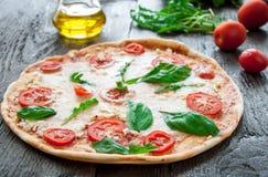 Pizza italiana rustica con la mozzarella, il formaggio ed il basilico Fotografie Stock Libere da Diritti