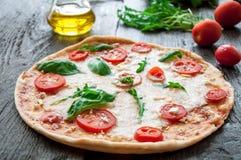 Pizza italiana rustica con la mozzarella, il formaggio ed il basilico Immagine Stock