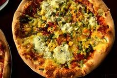 Pizza italiana sulla tavola di legno con gli ingredienti Fotografia Stock