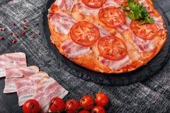 Pizza italiana tradicional com mozzarella, presunto, tomates foto de stock