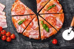 Pizza italiana tradicional com mozzarella, presunto, tomates, pimenta, especiarias dos pepperoni e o rucola fresco fotografia de stock