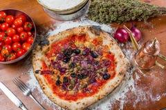 Pizza italiana tradicional con el atún, las cebollas, la alcaparra y las aceitunas, o Imagen de archivo
