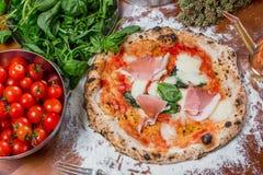 Pizza italiana tradicional con la mozzarella, el tomate, el jamón y el ingre Foto de archivo libre de regalías