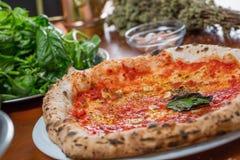 Pizza italiana tradicional con la salsa de tomate, el ajo y la albahaca, o Foto de archivo