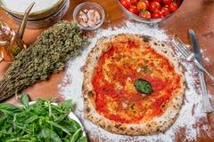 Pizza italiana tradicional con la salsa de tomate, el ajo y la albahaca, o Imágenes de archivo libres de regalías