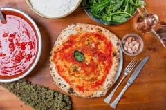 Pizza italiana tradicional con la salsa de tomate, el ajo y la albahaca, o Foto de archivo libre de regalías