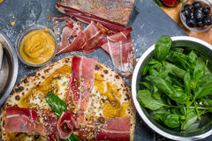 Pizza italiana tradicional con pesto, el jamón, queso Gorgonzola y las semillas de la calabaza Imagen de archivo